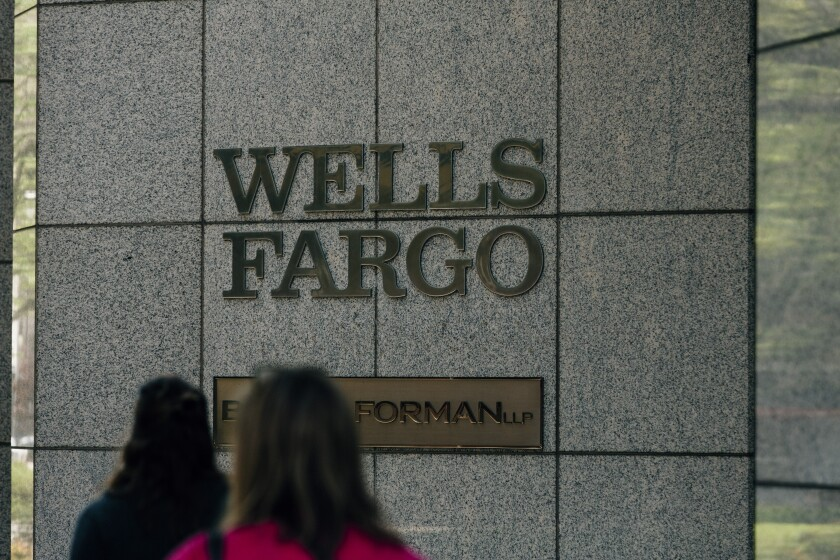 Pedestrians pass in front of the Wells Fargo & Co. corporate office in Birmingham, Alabama, U.S., on Wednesday, April 11, 2018. Wells Fargo & Co. is scheduled to release earnings figures on April 13. Photographer: Wes Frazer/Bloomberg