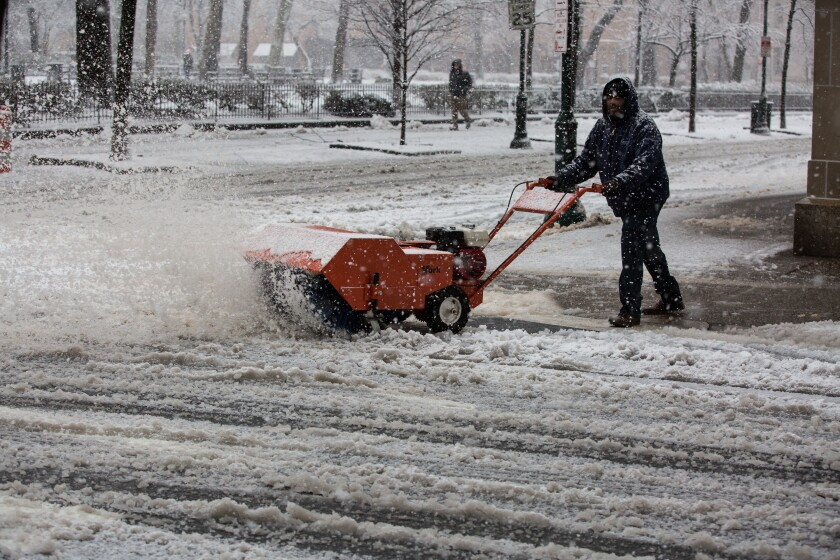 A resident uses a snowblower to clear a sidewalk during Winter Storm Quinn in Philadelphia, Pennsylvania, U.S., on Wednesday, March 7, 2018.