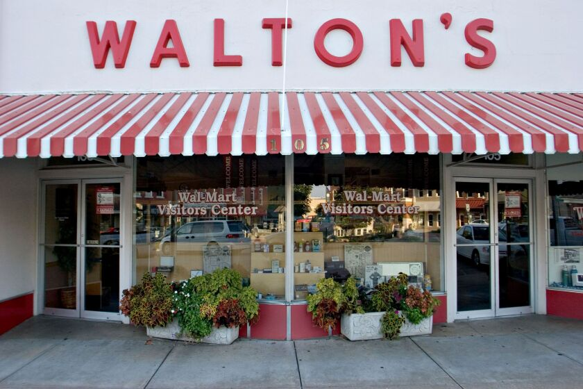 A sign for Walton's 5&10, the forerunner to today's Wal-Mart stores, hangs above what now serves as the Wal-Mart Visitors Center in Bentonville, Arkansas, U.S. Thursday, Sept. 20, 2007. The Walton's store was opened by Sam Walton on May 9, 1950. Photographer: JB Reed/ Bloomberg News