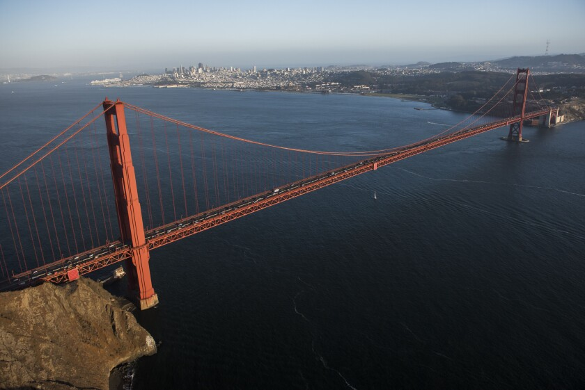 Cars travel across the Golden Gate Bridge in this aerial photograph taken above San Francisco, California, U.S., on Monday, Oct. 5, 2015. With tech workers flooding San Francisco, one-bedroom apartment rents have climbed to $3,500 a month, more than in any other U.S. city. Photographer: David Paul Morris/Bloomberg