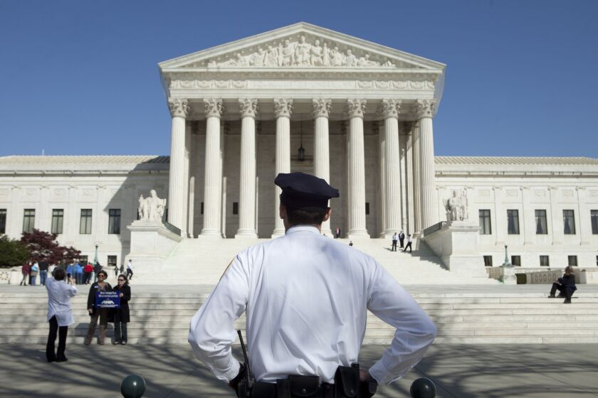 A police officer stands in front of the Supreme Court building in Washington, D.C., U.S., on Monday, March 26, 2012. The Supreme Court opens today its historic review of President Barack Obama's health-care law, three days of arguments that might result in the president's premier legislative achievement being found unconstitutional in the middle of his re-election campaign. Photographer: Andrew Harrer/Bloomberg