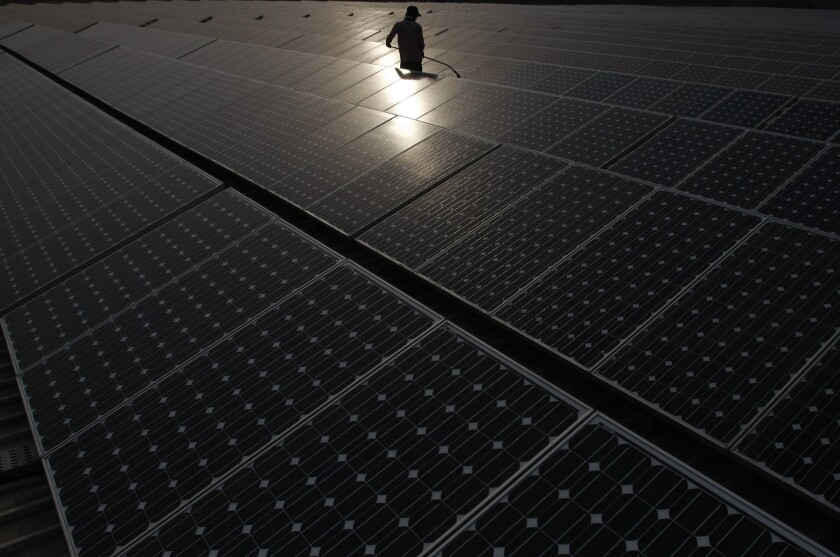 A maintenance worker cleans solar panels at a power station in New Delhi, India.