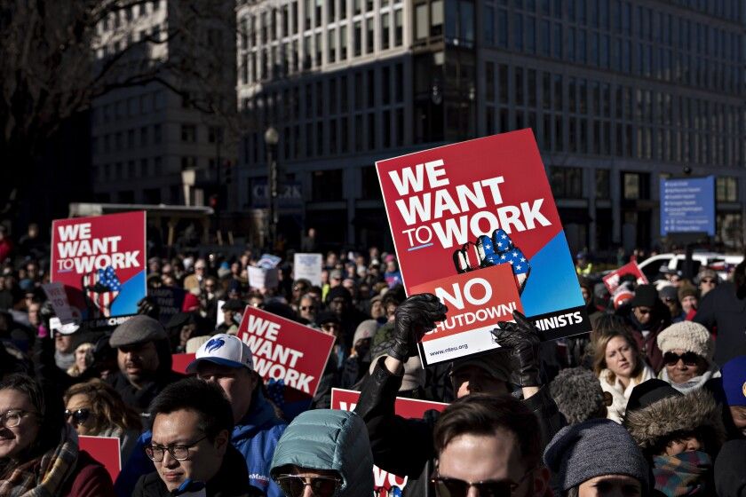 "A demonstrator holds a ""We Want To Work"" sign during a rally with union members and federal employees to end the partial government shutdown outside the American Federation of Labor & Congress of Industrial Organizations (AFL-CIO) headquarters in Washington, D.C., U.S., on Thursday, Jan. 10, 2019. The partial government shutdown entered its 20th day today as its impact is more widely felt with about 800,000 federal workers who will miss their paychecks on Friday."