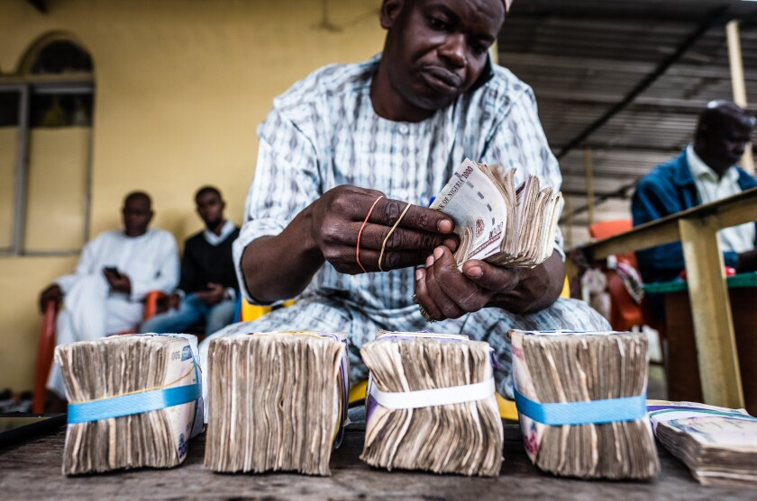 A currency dealer uses a mobile phone as he counts bundles of Nigerian naira banknotes for exchange on the 'black market' in Lagos, Nigeria.