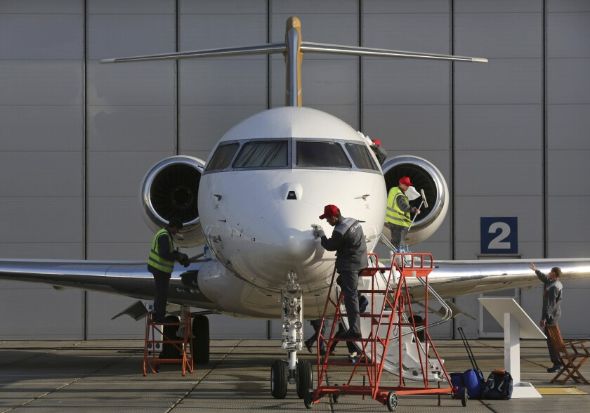 Workers prepare a Bombardier Global 6000 aircraft ahead of the Jet Expo 2012 exhibition at Vnukovo airport in Moscow.