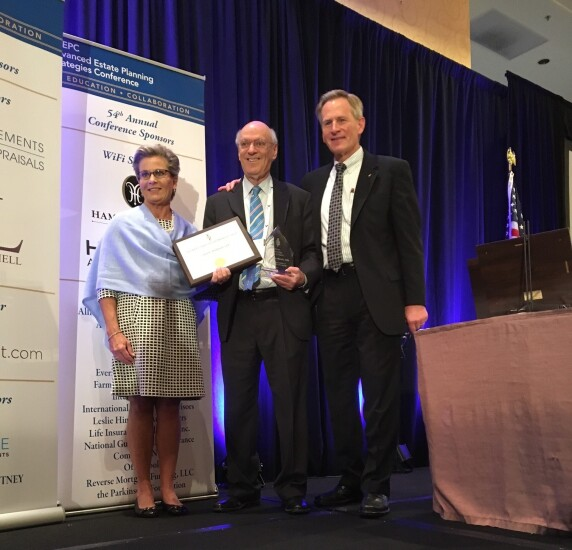 Julie Buschman, chairperson of the AEP designation, and Paul Viren, president of NAEPC, present an award to Edward Mendlowitz
