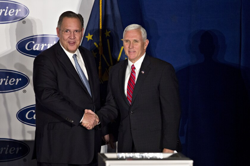 Gregory Hayes, president and chief executive officer of United Technologies Corp., left, shakes hands with U.S. Vice President-elect Mike Pence during an event at Carrier Corp. in Indianapolis, Indiana, U.S., on Thursday, Dec. 1, 2016.