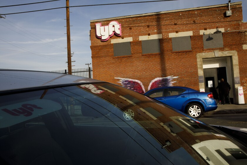 Vehicles sit parked outside the Lyft Inc. driver hub in Los Angeles.