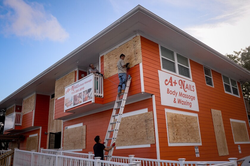A worker stands on a ladder while securing plywood to windows ahead of Hurricane Florence in Carolina Beach, North Carolina, U.S., on Tuesday, Sept. 11, 2018. Hurricane Florence could be the most powerful storm to make landfall in North Carolina if predictions hold — no Category 4 hurricane has ever made landfall in the state. Photographer: Charles Mostoller/Bloomberg