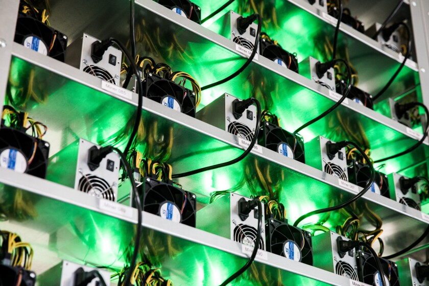Cryptocurrency mining rigs composed of Antminer S9 ASIC machines operate on racks.