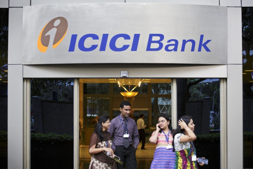 People exit an entrance of ICICI Bank Ltd.'s head office in Mumbai, India.