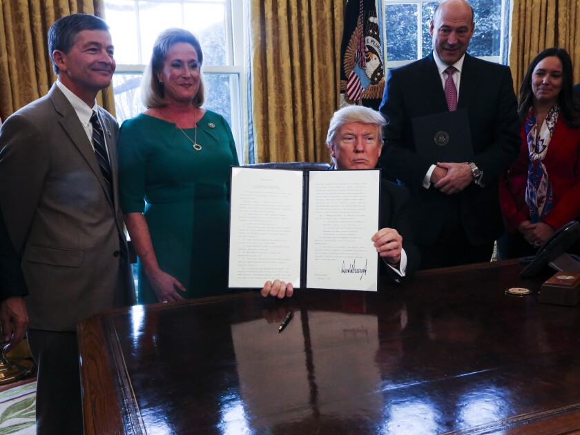 President Trump with members of Congress signing Dodd-Frank and fiduciary executive order Bloomberg News