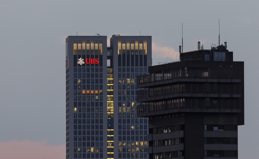 The UBS Group AG logo sits illuminated on the bank's skyscraper offices at dusk in Frankfurt, Germany, on Tuesday, July 17, 2018. Frankfurt's efforts to attract bankers escaping Brexit are in danger of losing momentum. Photographer: Alex Kraus/Bloomberg