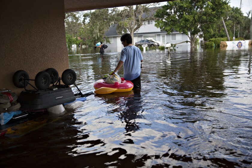 A resident collects personal belongings from his flooded home in Bonita Springs, Florida, after Hurricane Irma.