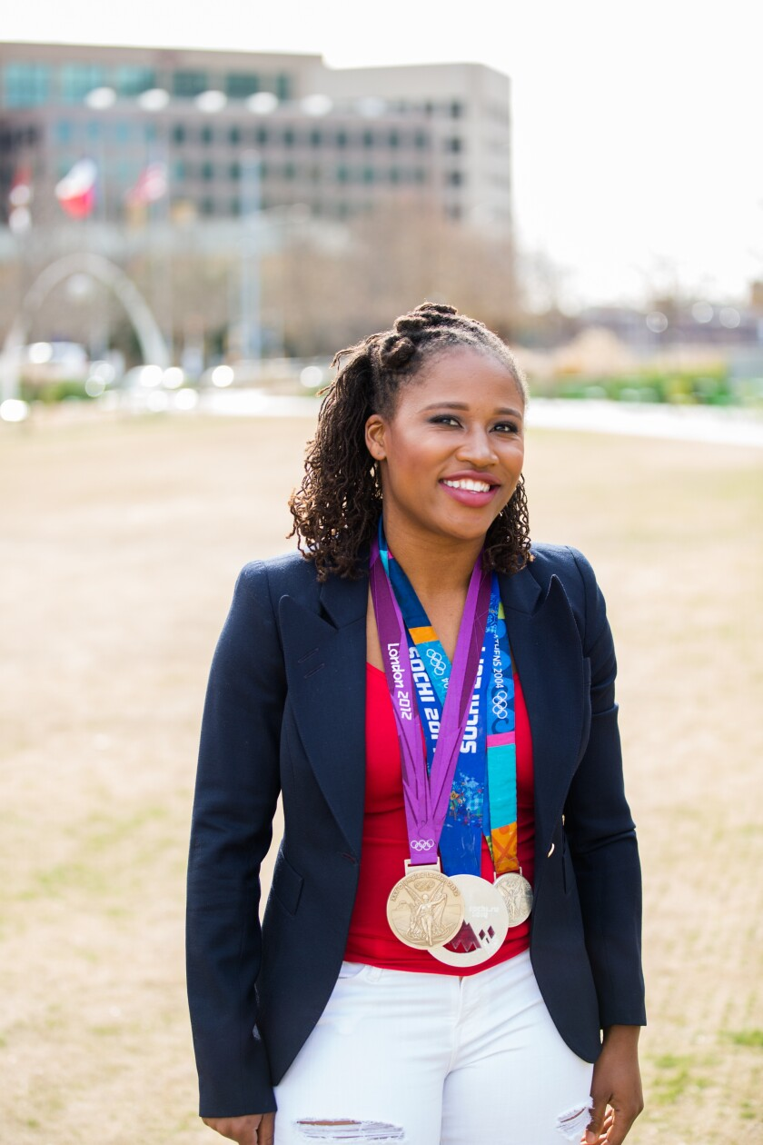 Financial advisor Lauryn Williams stands with her Olympic medals from track and bobsled.