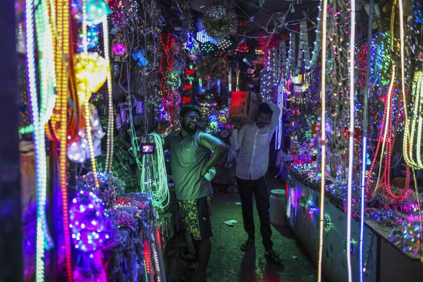 A customer browses a light system at a wholesale shop near a market in Mumbai, India.