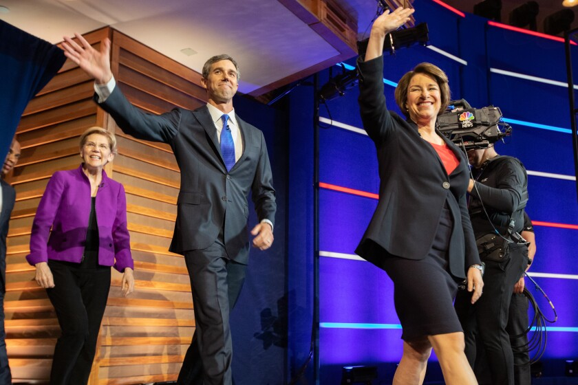 2020 Democratic presidential candidates Senator Amy Klobuchar, a Democrat from Minnesota, from right, Beto O'Rourke, former Representative from Texas, Senator Elizabeth Warren, a Democrat from Massachusetts, and Senator Cory Booker, a Democrat from New Jersey, arrive on stage during the Democratic presidential candidate debate in Miami, Florida, U.S., on Wednesday, June 26, 2019. Democratic presidential candidates tangled on health care in their first debate Wednesday, agreeing on the need for universal coverage but disagreeing about whether private insurance should be maintained. Photographer: Jayme Gershen/Bloomberg