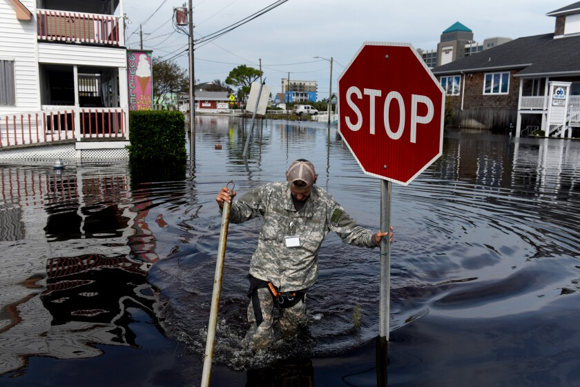 A member of a private critical crisis search and rescue team holds a stop sign as he wades through floodwaters after Hurricane Florence hit in Carolina Beach, North Carolina, U.S., on Monday, Sept. 17, 2018.