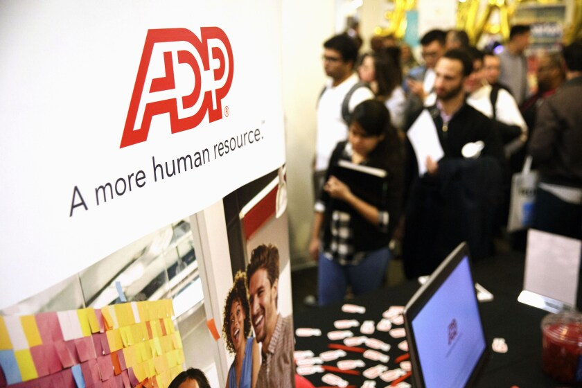 An ADP sign is on display as job seekers wait in line during the TechFair LA job fair in Los Angeles.