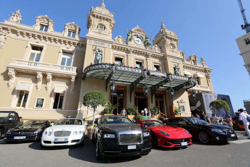 Luxury automobiles parked in front of the Casino de Monte-Carlo in Monaco. (Bloomberg News)