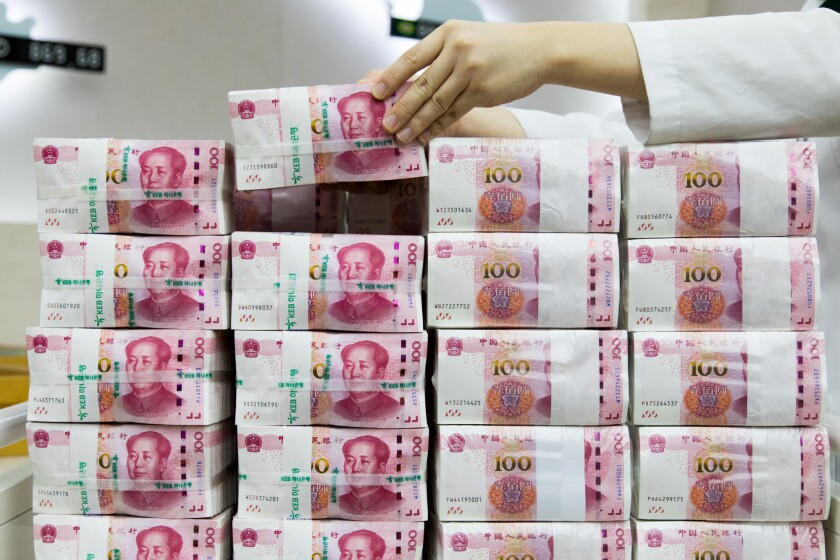 An employee arranges genuine bundles of Chinese one-hundred yuan banknotes at the Counterfeit Notes Response Center of KEB Hana Bank in Seoul, South Korea.