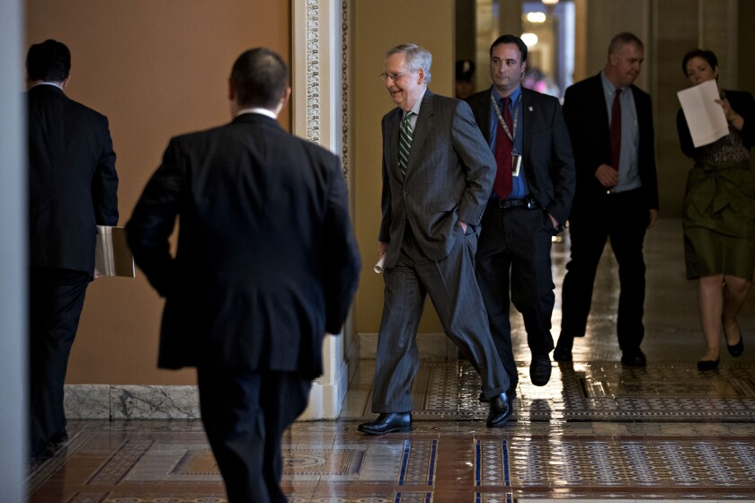 Senate Majority Leader Mitch McConnell, a Republican from Kentucky, center, walks to a private GOP meeting at the U.S. Capitol in Washington, D.C.,  on the day of the unveiling of the GOP health care bill