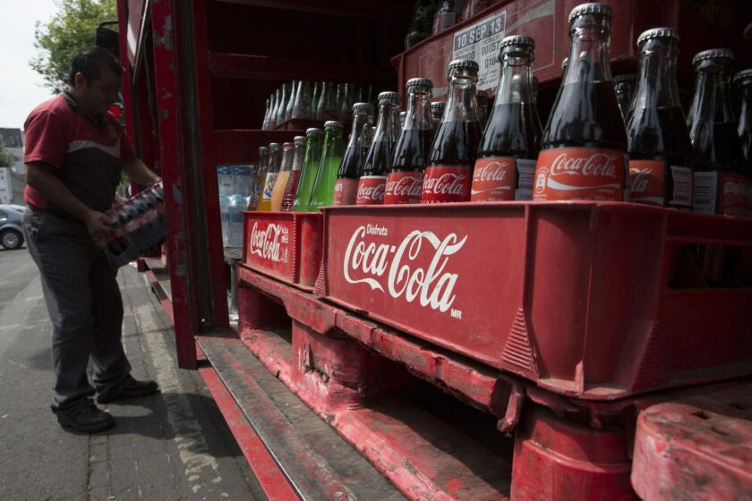 A delivery employee of Coca cola company unloads a package of Coca cola bottles from the delivery truck in the Zona Rosa area in Mexico city, Mexico, on Wednesday, April 2st, 2014. Photo:Susana González/Bloomberg