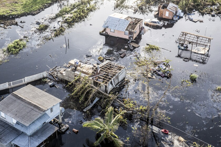 Destroyed homes and vehicles sit in floodwaters after Hurricane Maria Hamacao, Puerto Rico, on Monday, Sept. 25, 2017 Bloomberg News