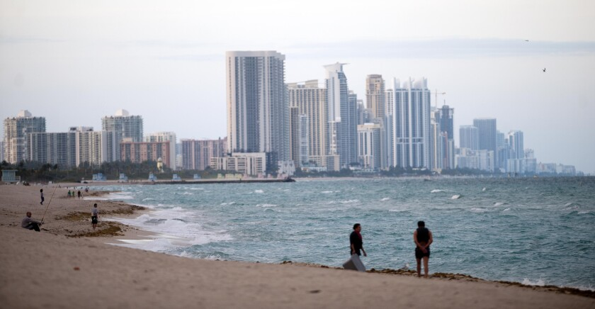 People stand on the shore in front of the skyline of Miami Beach, Florida.