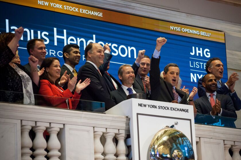 Richard Weil, co-chief executive officer of Janus Henderson Group PLC, center left, and Andrew Formica, co-chief executive officer of Janus Henderson Group PLC, center, ring the opening bell on the floor of the New York Stock Exchange (NYSE) in New York, U.S., on Friday, June 2, 2017. U.S. stocks were little changed following monthly payrolls data that fell short of expectations. Photographer: Michael Nagle/Bloomberg