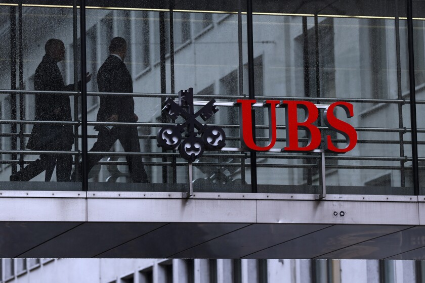 Employees pass between offices as the UBS logo sits on a walkway at the bank's headquarters in Zurich, Switzerland, on Monday, Jan. 22, 2018.