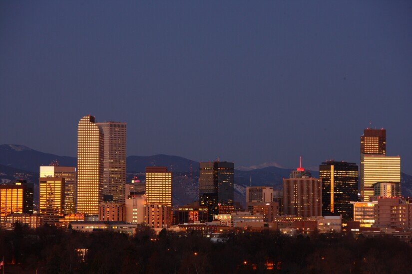 The Rocky Mountains form the backdrop to the city's skyline in Denver, Colorado, U.S.
