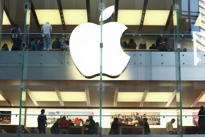 Customers shops in an Apple Inc. store in Sydney, Australia.