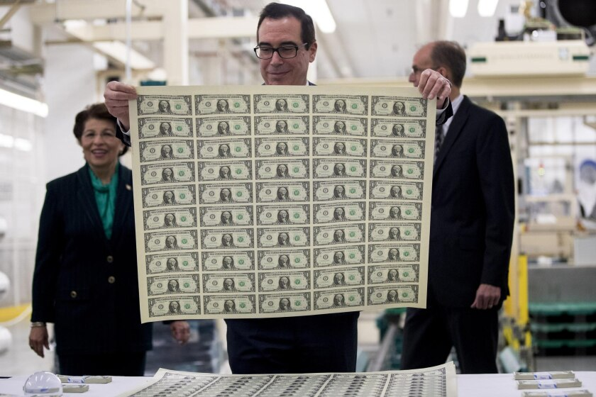 Treasury Secretary Steven Mnuchin views an uncut sheet of $1 notes bearing his name at the U.S. Bureau of Engraving and Printing in Washington, D.C.