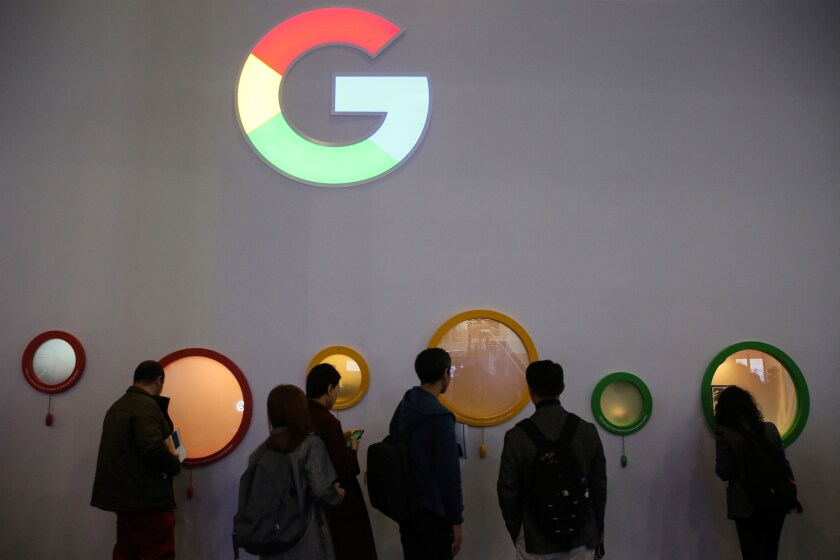 Attendees peer through portholes on the Google Inc. stand on the opening day of the MWC Barcelona in Barcelona, Spain.