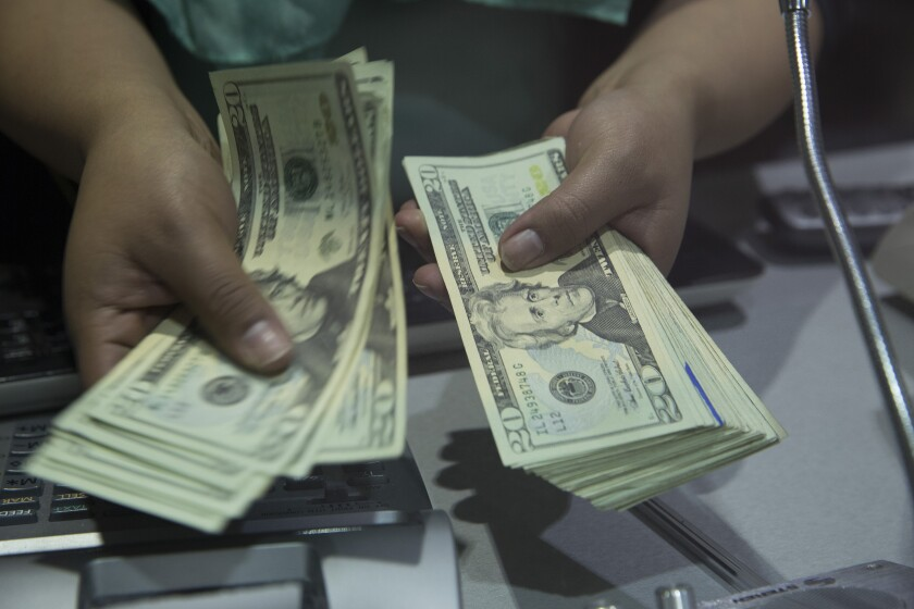 A worker counts U.S. twenty dollar bills inside a currency exchange store at the Benito Juarez International Airport in Mexico City, Mexico, on Monday, Feb. 15, 2016. Mexico's peso led world gains, climbing the most in more than four years, as Banxico was said to sell dollars directly to banks to support the currency. Photographer: Susana Gonzalez/Bloomberg