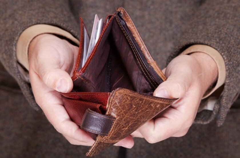Broke businessman showing brown leather empty wallet. Business concept- finance and poor economy.