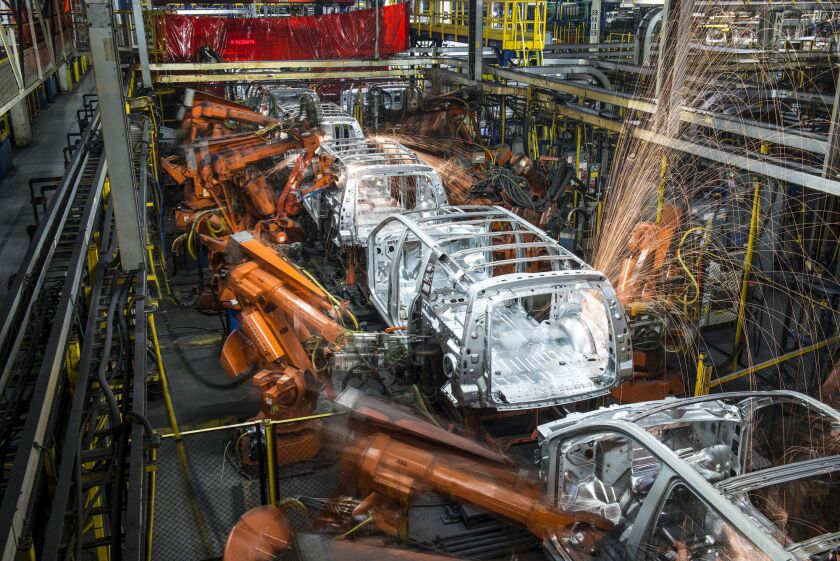Robotic machines weld together the frames of sports utility vehicles during production at the General Motors assembly plant in Arlington, Texas.