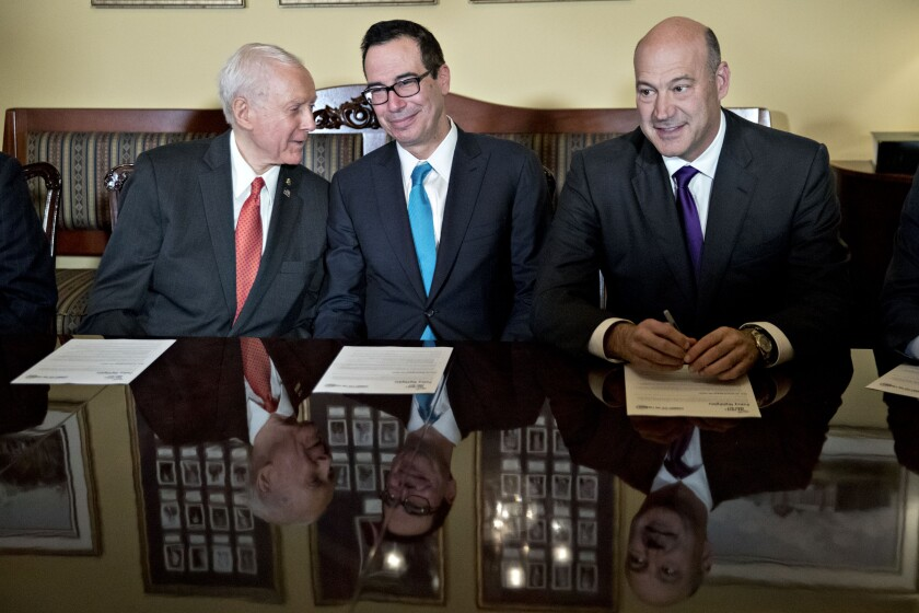 Senator Orrin Hatch, a Republican from Utah and chairman of the Senate Finance Committee, left, talks to Steven Mnuchin, U.S. Treasury Secretary, as Gary Cohn, director of the U.S. National Economic Council, right, sits during a meeting with members of the committee on tax reform legislation at the U.S. Capitol in Washington, D.C., U.S., on Thursday, Nov. 9, 2017. Senate Republicans released their vision for a tax-cut plan Thursday that would cut the corporate tax rate to 20 percent, with a one-year delay to 2019, as Congress moves quickly to fulfill one of the GOPs biggest and most long-awaited goals. Photographer: Andrew Harrer/Bloomber