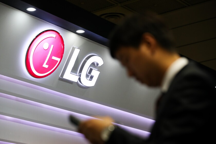 A visitor checks a smartphone in front of an LG Electronics Inc. logo displayed at the World IT Show 2018 in Seoul, South Korea/