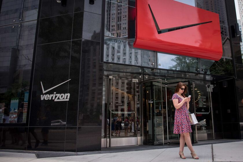 A pedestrian uses a smartphone outside a Verizon Communications Inc. store in downtown Chicago.