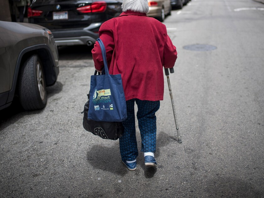 A photo of an elderly woman walking with a cane